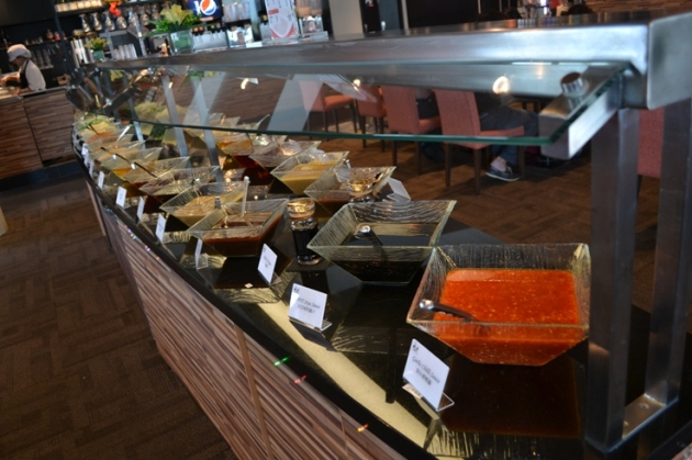 Condiment buffet which includes chives, sliced leaks, soya sauce, chili oil, garlic oil, sesame sauce, chopped chilli, parsley, vinegar, fried and raw chopped garlic, etc.